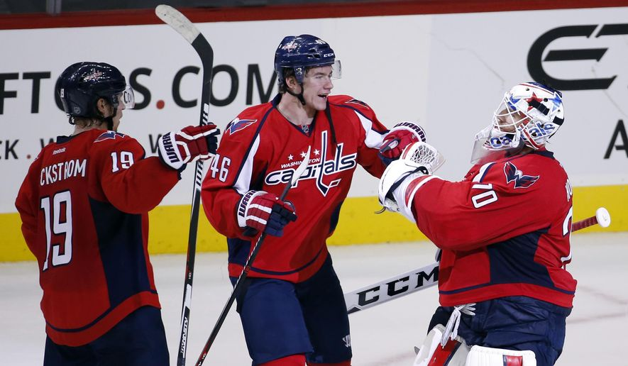 Washington Capitals center Nicklas Backstrom (19), from Sweden, and Capitals center Michael Latta (46) celebrate with Capitals goalie Braden Holtby (70) after an NHL hockey game against the Detroit Red Wings, Tuesday, Dec. 8, 2015, in Washington. The Capitals won 3-2 in a shootout. (AP Photo/Alex Brandon)