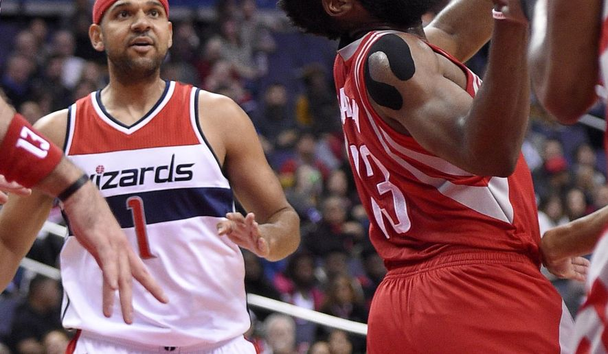 Houston Rockets guard James Harden (13) looks for the ball as Washington Wizards guard Jared Dudley (1) looks on during the first half of an NBA basketball game, Wednesday, Dec. 9, 2015, in Washington. (AP Photo/Nick Wass)