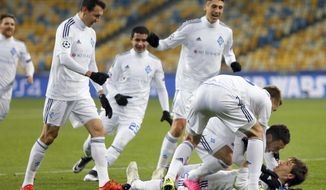 Kiev's Denys Garmash, right, is lying on the pitch as he celebrates after scoring the opening goal during the Champions League Group G soccer match between Dynamo Kiev and Maccabi Tel Aviv at the Olympiyskiy national stadium in Kiev, Ukraine, Wednesday, Dec. 9, 2015. Kiev defeated Tel Aviv by 1-0. (AP Photo/Sergei Chuzavkov)