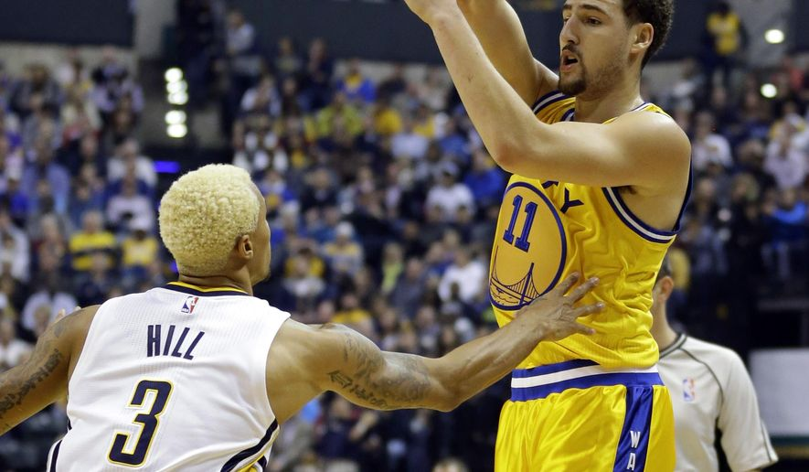 Golden State Warriors guard Klay Thompson (11) passes over Indiana Pacers guard George Hill (3) during the first half of an NBA basketball game in Indianapolis, Tuesday, Dec. 8, 2015. (AP Photo/Michael Conroy)