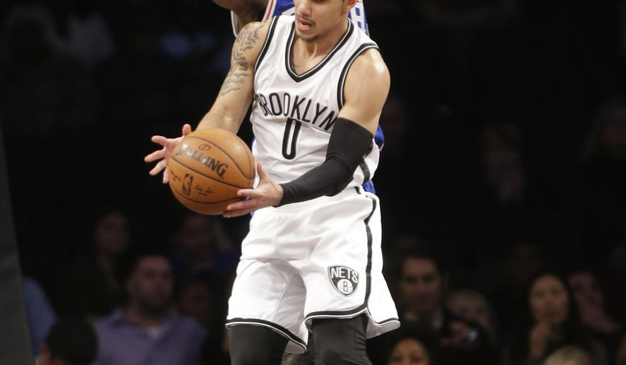 Brooklyn Nets' Shane Larkin (0) passes the ball away from Philadelphia 76ers' Nerlens Noel (4) during the first half of an NBA basketball game Thursday, Dec. 10, 2015, in New York. (AP Photo/Frank Franklin II)