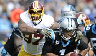 Carolina Panthers' Cam Newton (1) is hit by Washington Redskins' Jason Hatcher (97) defends in the first half of an NFL football game in Charlotte, N.C., Sunday, Nov. 22, 2015. (AP Photo/Mike McCarn)