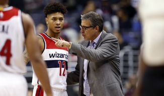 Washington Wizards forward Kelly Oubre Jr. (12) listens to Washington Wizards head coach Randy Wittman in the second half of an NBA basketball game against the Milwaukee Bucks, Tuesday, Nov. 17, 2015, in Washington. The Wizards won 115-86. (AP Photo/Alex Brandon)