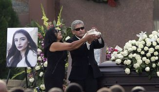 The parents Yvette Velasco release a dove of during a memorial service on Thursday, Dec. 10, 2015 in Covina, Calif. Velasco died in a mass shooting in San Bernardino, Calif., that killed 14 and injured 21 last Wednesday. (AP Photo/Chris Carlson)