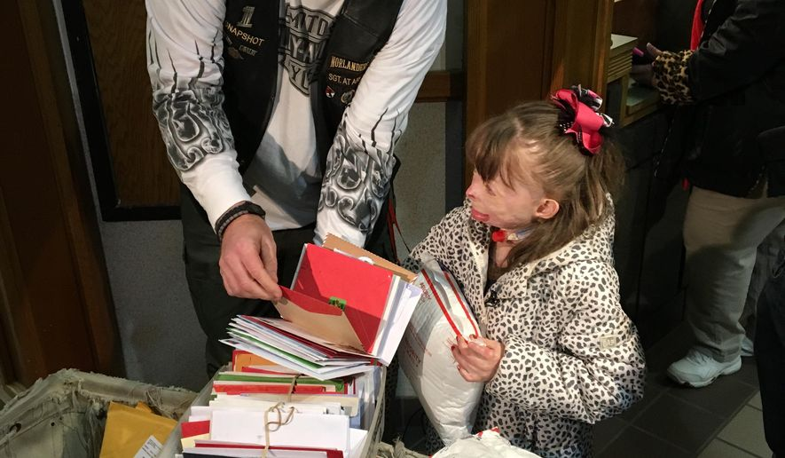 Safyre Terry, 8, and Kevin Clark collect cards and gifts on Wednesday, Dec. 9, 2015, at a post office near her home in Rotterdam, N.Y.  Terry, who lost her father and three younger siblings and was burned over 75 percent of her body in a May 2013 house fire, has been receiving cards from across the country since her custodial aunt posted a Facebook photo of her saying she wants cards for a Christmas tree display stand. Clark, a member of a motorcycle club that participated in a benefit for Safyre this fall, shared the original post and said it has been shared tens of thousands of times all over the world.  A crowd funding site has generated more than $177,000 for the family. (AP Photo/Mary Esch)