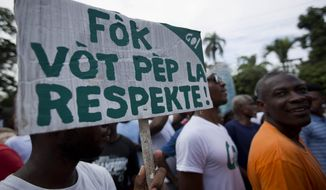 """A demonstrator holds up a banner that reads in Creole """"The Vote of the population has to be respected"""" during a protest by the Haitian rights groups against the country's electoral council in Port-au-Prince, Haiti, Thursday Dec. 10, 2015. The disputed election results have brought a renewed surge of paralyzing street protests and so many broad accusations of electoral fraud from civil society and opposition groups it is not clear whether a Dec. 27 presidential runoff between the top two finishers can take place as scheduled. (AP Photo/Dieu Nalio Chery)"""