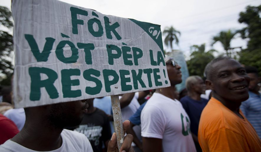"A demonstrator holds up a banner that reads in Creole ""The Vote of the population has to be respected"" during a protest by the Haitian rights groups against the country's electoral council in Port-au-Prince, Haiti, Thursday Dec. 10, 2015. The disputed election results have brought a renewed surge of paralyzing street protests and so many broad accusations of electoral fraud from civil society and opposition groups it is not clear whether a Dec. 27 presidential runoff between the top two finishers can take place as scheduled. (AP Photo/Dieu Nalio Chery)"
