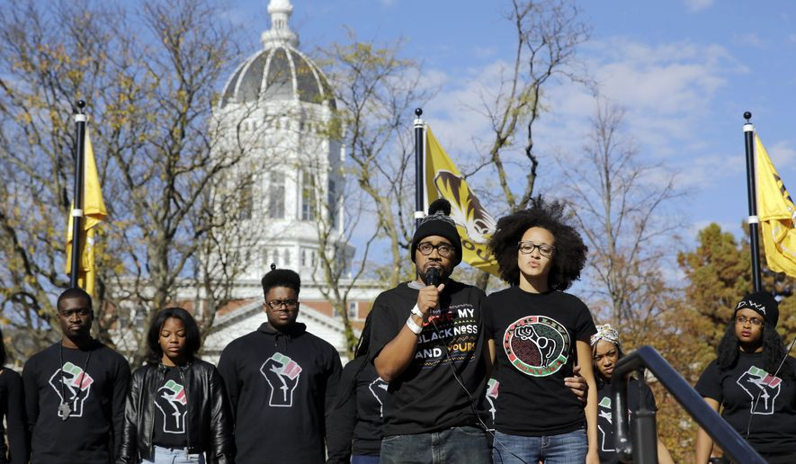 In this Nov. 9, 2015 photo, Jonathan Butler, center, addresses a crowd in Columbia following the resignation of University of Missouri System President Tim Wolfe after days of protests over concerns about the administration's handling of racial issues. (AP Photo/Jeff Roberson/File)