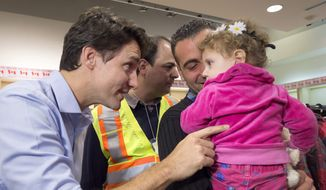 Prime Minister Justin Trudeau, left, greets Madeleine Jamkossian, right, and her father Kevork Jamkossian, refugees fleeing the Syria, during their arrival at Pearson International airport, in Toronto, on Friday, Dec. 11, 2015. The first Canadian government plane carrying Syrian refugees arrived in Toronto late Thursday. (Nathan Denette/The Canadian Press via AP)