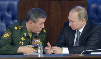 Russian President Vladimir Putin, right, speaks with Chief of the General Staff of the Russian Armed Forces Valery Gerasimov  at a meeting with top military officials in the National Defense Control Center in Moscow, Russia, Friday, Dec. 11, 2015. President Vladimir Putin said that a Russian military action in Syria is aimed at protecting Russia from extremists based there. (Alexei Druzhinin/Sputnik, Kremlin Pool Photo via AP)