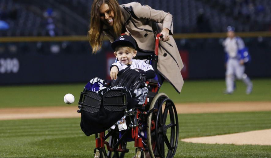 FILE - In this May 8, 2015, file photo, two-year-old Jameson Axford throws out the ceremonial first pitch as his mother, Nicole, looks on before the Colorado Rockies host the Los Angeles Dodgers in a baseball game in Denver. Little Jameson is running around like a typical toddler these days, nine months after the son of reliever John Axford received a rattlesnake bite at spring training that threatened his life. (AP Photo/David Zalubowski, File)