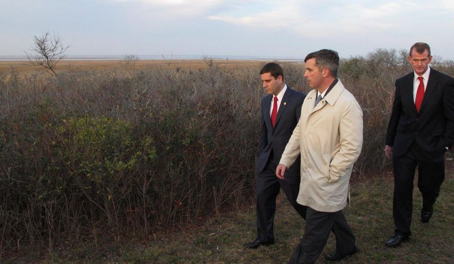"""Deputy Suffolk County Police Commissioner Tim Sini, left, homicide Detective Lt. Kevin Beyrer, center, and Chief of Department Stuart Cameron tour a remote area off a Long Island parkway Friday, Dec. 11, 2015, where the bodies of 10 people were discovered in 2010 and 2011, in Babylon, N.Y. Sini, who has been nominated to be the new police commissioner, has announced a renewed effort at finding those responsible for the killings in what has become known as the """"Long Island serial killer"""" case. Friday marked the fifth anniversary of when the first of the victims were found. The body of an 11th woman also was found several miles away, but detectives do not believe her death is linked to the other 10. (AP Photo/Frank Eltman)"""