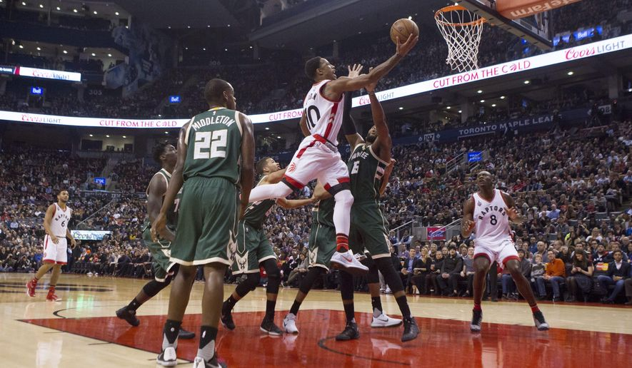 Toronto Raptors' DeMar DeRozan, center, scores against Milwaukee Bucks' Greg Monroe (15) as Bucks' Khris Middleton (22) looks on during first-half NBA basketball game action in Toronto, Friday, Dec. 11, 2015. (Chris Young/The Canadian Press via AP) MANDATORY CREDIT