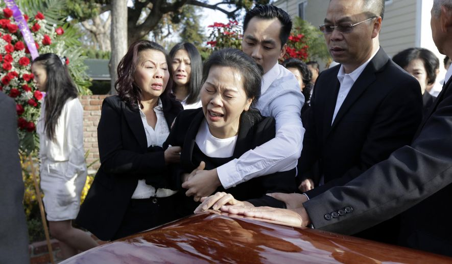 Trung Do embraces his mother Van Thanh Nguyen, center, mother of Tin Nguyen, as she weeps over her daughter's coffin during the wake at the Peek Funeral home in Westminster, Calif., Friday, Dec. 11, 2015. Nguyen died in the mass shooting in San Bernardino, Calif., on Dec. 2. (AP Photo/Nick Ut)