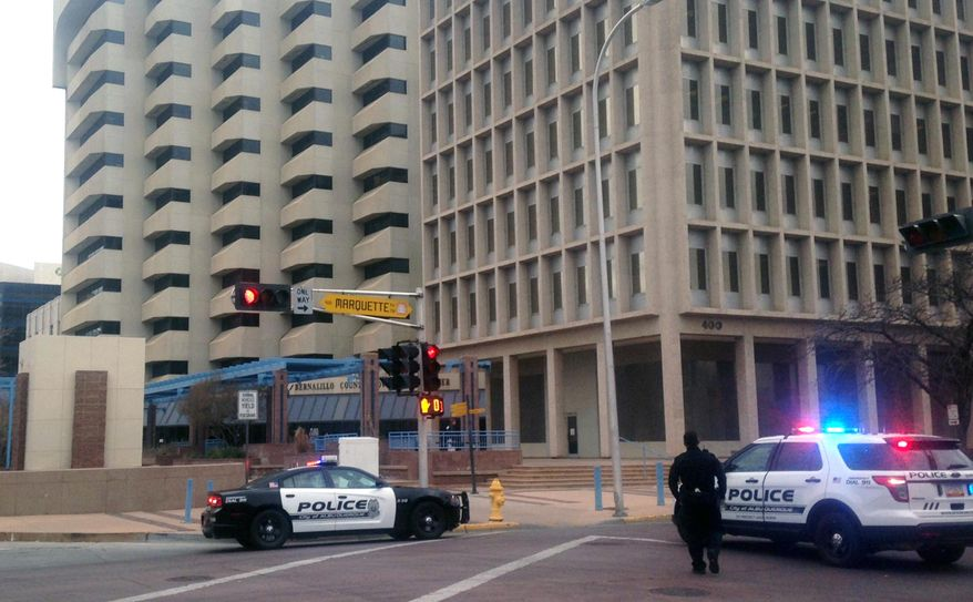Police gather outside of Albuquerque City Hall, Friday, Dec. 11, 2015. Authorities say City Hall has been placed on lockdown after witnesses say they saw a person with gun inside. Police said authorities don't believe an active shooter was in the area, which includes Downtown Albuquerque. However, a person was seen inside the building armed with a gun and causing a disturbance. (AP Photo/Mary Hudetz)