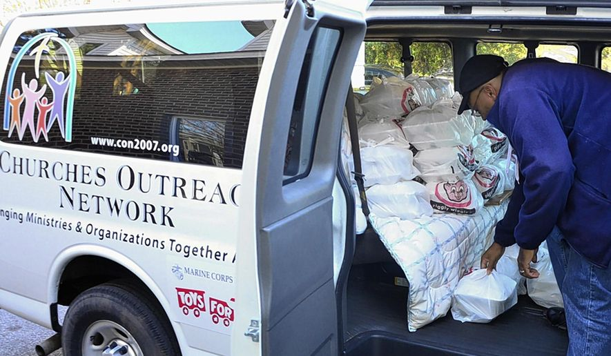 ADVANCE FOR THE WEEKEND OF DEC. 12-13 AND THEREAFTER - In a Saturday, Nov. 21, 2015 photo, Churches Outreach Network's van is filling up to deliver plates from the JOY Soup Kitchen's annual Thanksgiving dinner  in Greenville, N.C. (Bayardo Caceres-Rossel/The Daily Reflector)