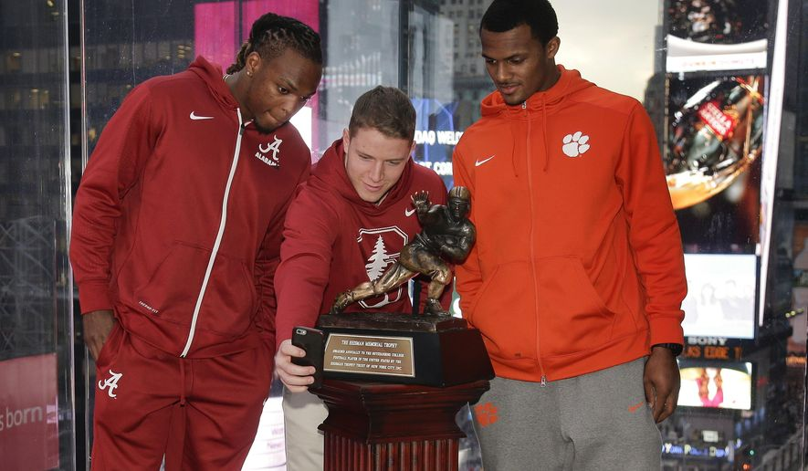 Heisman Trophy finalists, from left, Alabama's Derrick Henry, Stanford's Christian McCaffrey and Clemson's Deshaun Watson pose for a selfie above Times Square, Friday, Dec. 11, 2015, in New York. (AP Photo/Julie Jacobson)