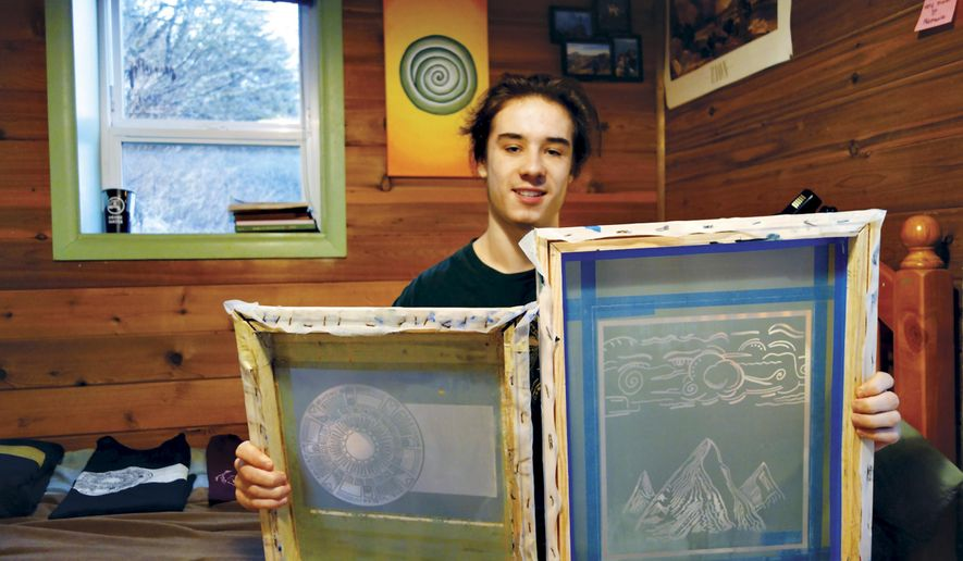 ADVANCE FOR WEEKEND DEC. 12-13, 2015 AND THEREAFTER - In this Nov. 27, 2015 photo, Juneau-Douglas High School student Noah Spengler holds up two of his silk-screens at his home in Juneau, Alaska. Spengler is a 17-year-old with a business he's created by hand. Spengler paints and draws, keeps sketches in a notebook and paintings on the walls of his family's home. Earlier this year, he found a way to get his artwork out into the world, and customers' closets, when he started a silk-screening business. And though it's just getting started, he's shipped t-shirts and sweatshirts with his designs as far as the United Kingdom and Australia. (Mary Catharine Martin/Capital City Weekly via AP)