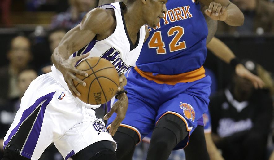 Sacramento Kings guard Rajon Rondo, left, drives against New York Knicks forward Lance Thomas during the first quarter of an NBA basketball game in Sacramento, Calif., Thursday, Dec. 10, 2015. (AP Photo/Rich Pedroncelli)