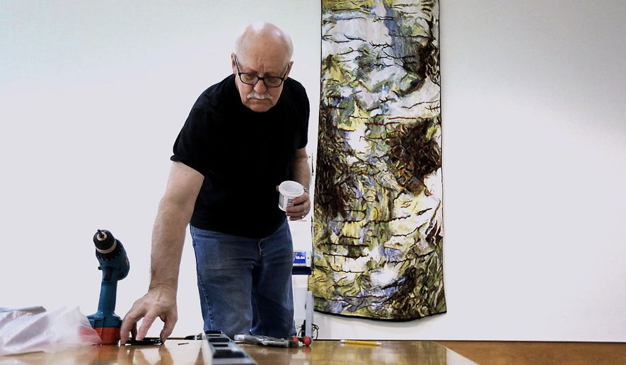 """Gene Jenneman works to hang an art piece for the new exhibit called """"Extreme Fibers: Textile Icons and the New Edge"""" at the Dennos Museum Center in Traverse City, Mich., Monday, Dec. 7, 2015. The new exhibition at the museum center features works by fiber artists such as a basket woven with cedar roots and a necklace braided from wool, nylon and pig intestines. (Tessa Lighty/Traverse City Record-Eagle via AP) MANDATORY CREDIT"""