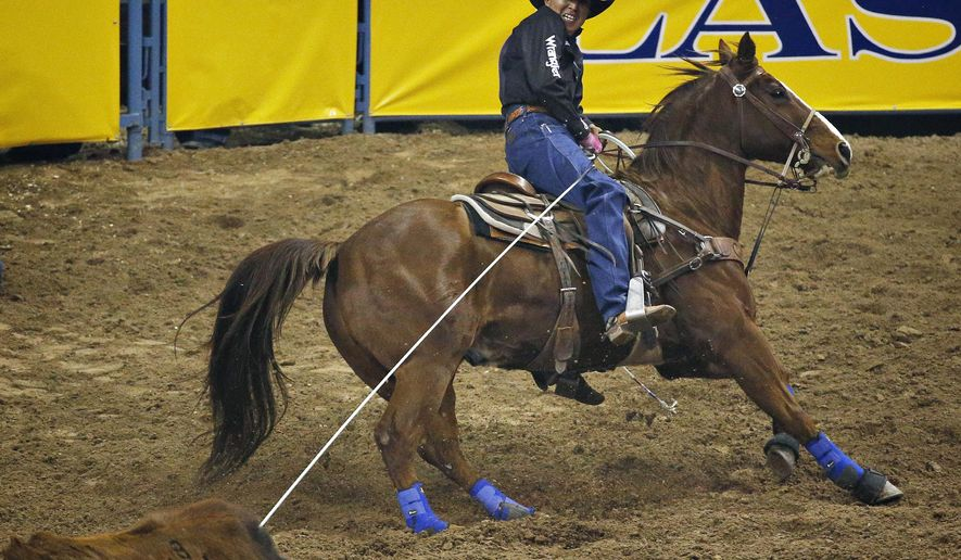 In this Dec. 10, 2015, photo, Derrick Begay competes in the team roping event during the eighth go-round of the National Finals Rodeo, in Las Vegas. (AP Photo/John Locher)
