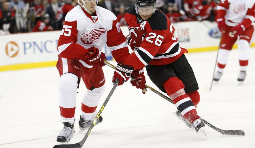 New Jersey Devils left wing Patrik Elias (26), of the Czech Republic, attacks against Detroit Red Wings defenseman Danny DeKeyser (65) during the second period of an NHL game, Friday, Dec. 11, 2015, in Newark, N.J. (AP Photo/Julio Cortez)