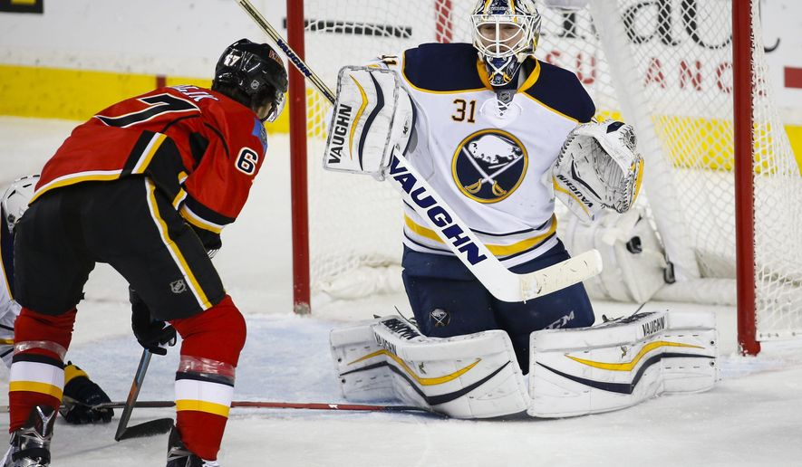 Buffalo Sabres' goalie Chad Johnson, right, deflects a shot from Calgary Flames' Michael Frolik, of the Czech Republic, during second-period NHL hockey game action in Calgary, Thursday, Dec. 10, 2015. (Jeff McIntosh/The Canadian Press via AP) MANDATORY CREDIT