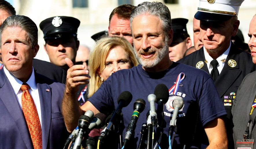 """FILE - In this Sept. 16, 2015 file photo, Comedian Jon Stewart stands with New York City first responders during a rally on Capitol Hill in Washington. Steward called for the extension of the the Zadroga Heath & Compensation Act that provides health care and compensation to 9/11 first responders and victims will come to an end if not renewed by Congress. Stewart  appeared with Stephen Colbert on the CBS """"Late Show,"""" Thursday Dec. 10, to push Congress to approve more funding to treat people sickened by working in the rubble of the World Trade Center following the Sept. 11 attacks. (AP Photo/Lauren Victoria Burke, File)"""