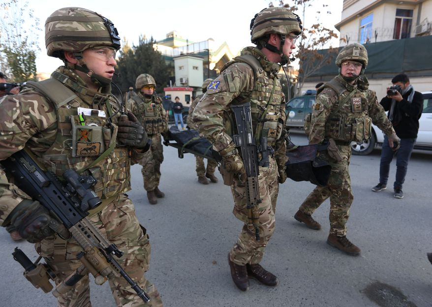 British soldiers carry the body of a victim of an attack that happened near the Spanish embassy, in Kabul, Afghanistan, Saturday, Dec. 12, 2015. Explosions and gunfire rocked a diplomatic area of central Kabul overnight as security forces tried to flush out Taliban attackers who claimed responsibility for a deadly car bomb Friday. (AP Photo/Rahmat Gul)