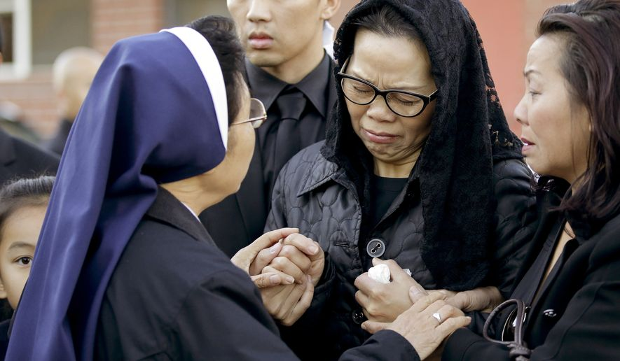 Van Thanh Nguyen, center, is greeted by a nun as she arrives for her daughter Tin Nguyen's funeral on Saturday, Dec. 12, 2015, in Santa Ana, Calif. Nguyen died in the mass shootings in San Bernardino, Calif., on Dec. 2. (AP Photo/Chris Carlson)
