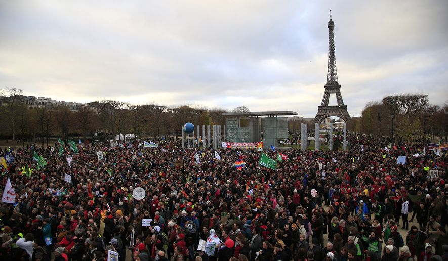Activists gather near the Eiffel Tower, in Paris, Saturday, Dec.12, 2015 during the COP21, the United Nations Climate Change Conference. As organizers of the Paris climate talks presented what they hope is a final draft of the accord, protesters from environmental and human rights groups gather to call attention to populations threatened by rising seas and increasing droughts and floods. (AP Photo/Thibault Camus)