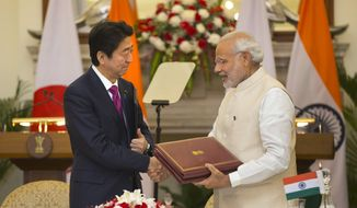 Indian Prime Minister Narendra Modi, right, shakes hand with his Japanese counterpart Shinzo Abe after signing of agreements, in New Delhi, India , Saturday, Dec. 12, 2015. India and Japan have signed agreements on military purchases for India's armed forces, high-speed trains and upgrading India's infrastructure.They also reached an agreement for cooperation in the peaceful use of nuclear energy, with the final deal to be signed after technical details are finalized.(AP Photo/Manish Swarup)