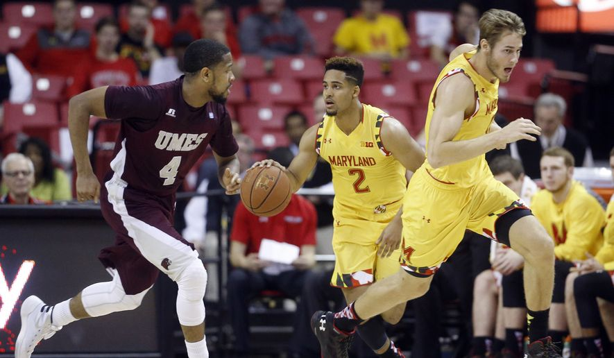 Maryland guard Melo Trimble (2) drives the ball behind teammate Jake Layman, right, and Maryland-Eastern Shore guard Devin Martin in the first half of an NCAA college basketball game, Saturday, Dec. 12, 2015, in College Park, Md. (AP Photo/Patrick Semansky)