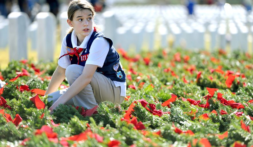 Amber Callon, 11, one of the American Heritage Girls in attendance, straightens the bows on the wreaths during Wreaths Across America Day at Jacksonville National Cemetery on Saturday, Dec. 12, 2015, in Jacksonville, Fla. Family and volunteers placed more than 7,000 wreaths on the headstones at the cemetery. (Bruce Lipsky/The Florida Times-Union via AP) MANDATORY CREDIT