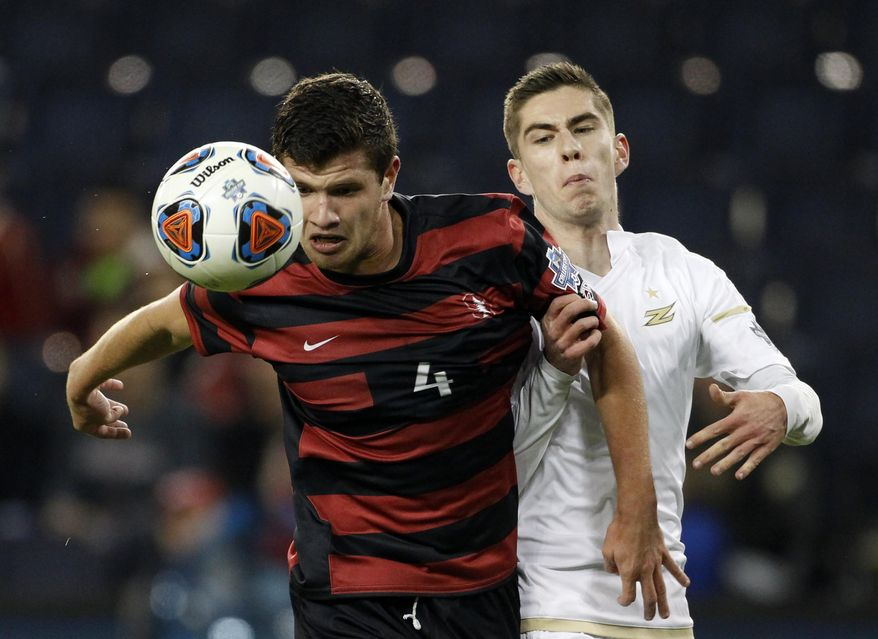 Stanford's Tomas Hilliard-Arce (4) is pressured by Akron's Stuart Holthusen (9) in the first half of an NCAA College Cup soccer match, Friday, Dec. 11, 2015, in Kansas City, Kan. (AP Photo/Colin E. Braley)
