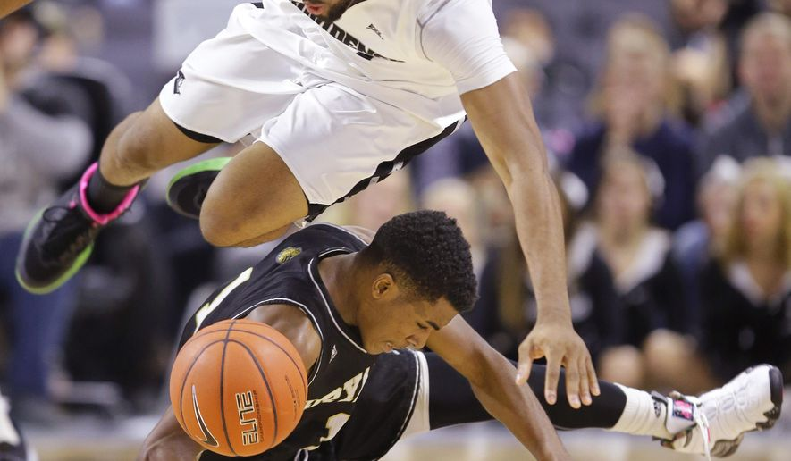 Providence guard Jalen Lindsey (21) flies through the air after being trip-up by Bryant guard Hunter Ware (1) while scrambling for a loose ball during the first half of their NCAA college basketball game  Saturday, Dec. 12, 2015, in Providence, R.I. (AP Photo/Stephan Savoia)