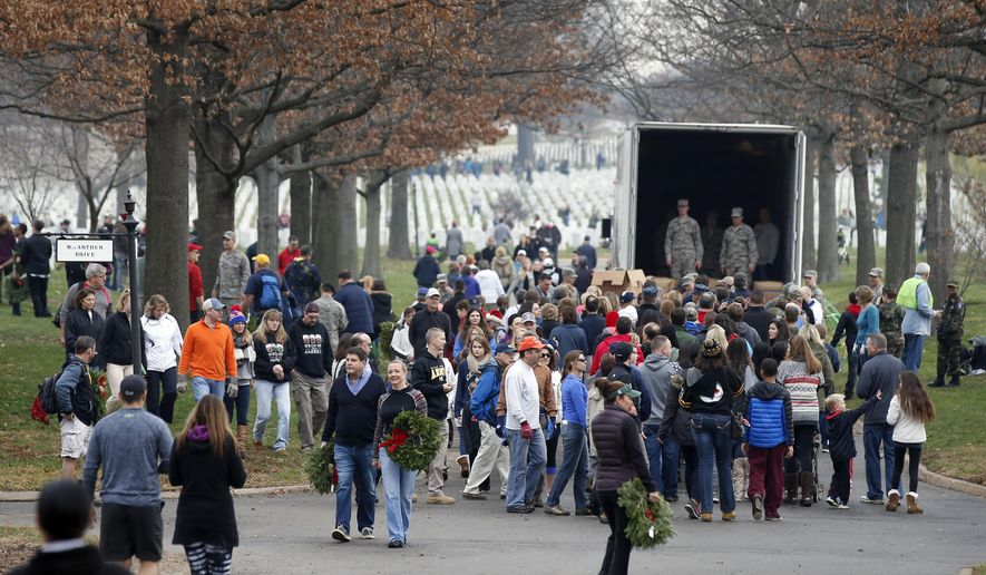 A crowd of volunteers gathers around a truck to get wreaths to place at graves as part of Wreaths Across America at Arlington National Cemetery in this file photo from Saturday, Dec. 12, 2015 in Arlington, Va. Organizers estimated that volunteers placed 240,815 wreaths at Arlington. (AP Photo/Alex Brandon) **FILE**