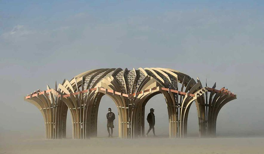 """FILE - In this Friday, Sept. 4, 2015 file photo, """"burners"""" stand inside an art sculpture during a dust storm at the Burning Man festival in the Black Rock Desert near Gerlach, Nev. Organizers of the Burning Man counter-culture celebration are challenging the enforcement of a Nevada state tax that they say could cost them nearly $3 million. Burning Man officials said in a letter to the state Department of Taxation on Friday, Dec. 12, 2015 that the festival should be exempt from the recently amended tax on live entertainment, the Reno Gazette-Journal reported Saturday. (Andy Barron/Reno Gazette-Journal via AP, File)"""