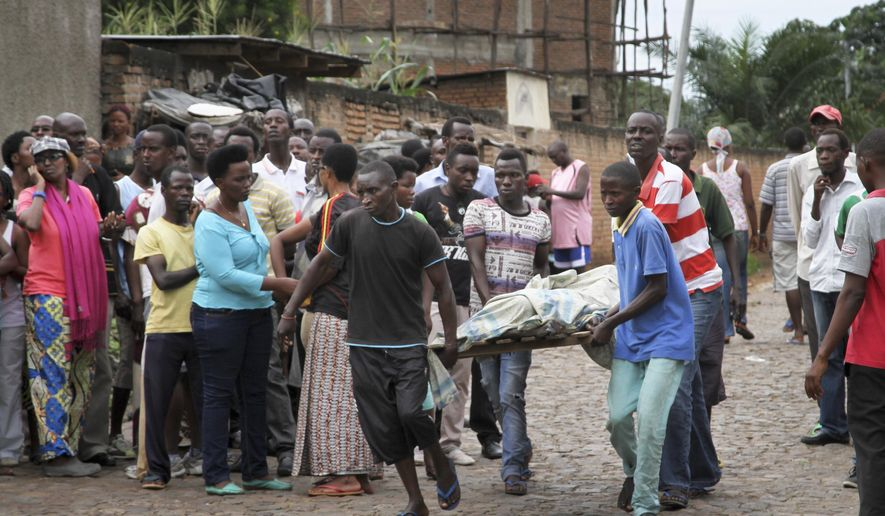 Men carry away a dead body in the Nyakabiga neighborhood of Bujumbura, Burundi, Saturday, Dec. 12, 2015. Burundi's political violence continued Saturday as a number of people were found shot dead in the Nyakabiga neighborhood of the capital, a day after the government said an unidentified group carried out coordinated attacks on three military installations. (AP Photo)