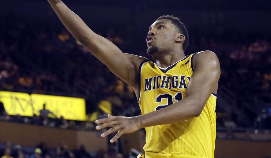 Michigan guard Zak Irvin (21) makes a layup during the second half of an NCAA college basketball game against Delaware State, Saturday, Dec. 12, 2015, in Ann Arbor, Mich. (AP Photo/Carlos Osorio)