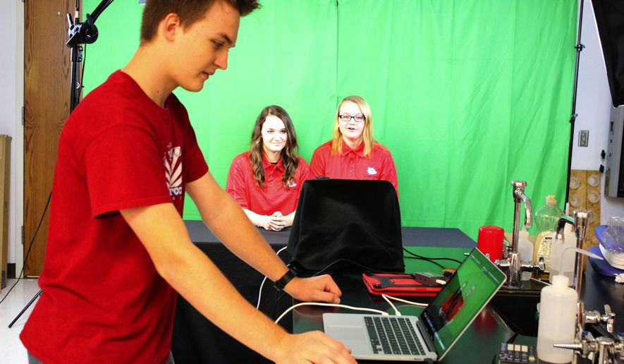 ADVANCE FOR THE WEEKEND OF DEC. 12-13 - In this Nov. 18, 2015 photo, Humphrey High School students Brandon Huettner works a computer while Jordan Martin, back, from left, and Monika Laudenklos wait to go on the air at K-DWG News at the school in Humphrey, Neb. Journalism students at the high school are taking to the airwaves to broadcast school news to their fellow students, family and friends. The broadcast can be viewed on the school's Facebook page for anyone in the community to watch. (Patrick Murphy/The Norfolk Daily News via AP) MANDATORY CREDIT