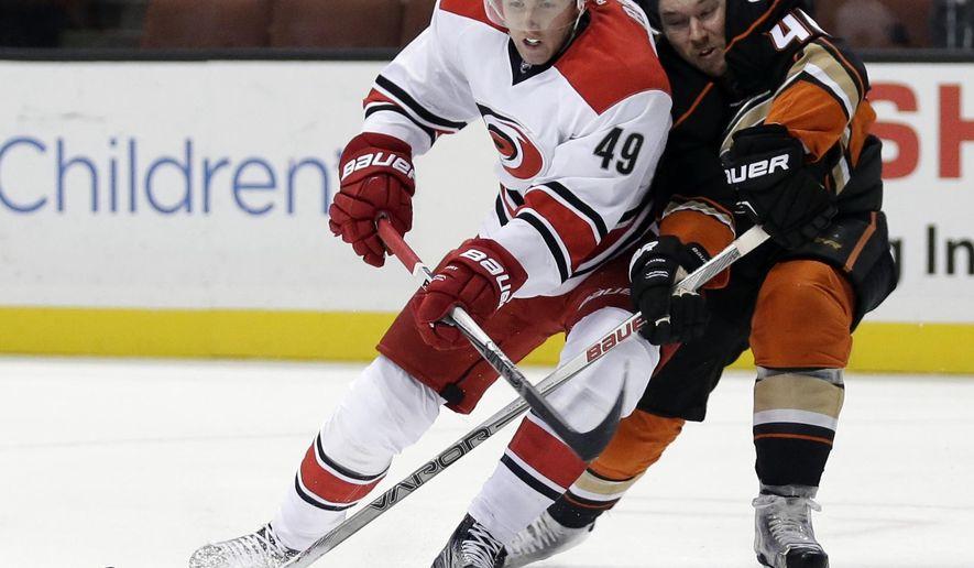 Carolina Hurricanes center Victor Rask, left, battles Anaheim Ducks defenseman Sami Vatanen for the puck during the first period of an NHL hockey game in Anaheim, Calif., Friday, Dec. 11, 2015. (AP Photo/Chris Carlson)