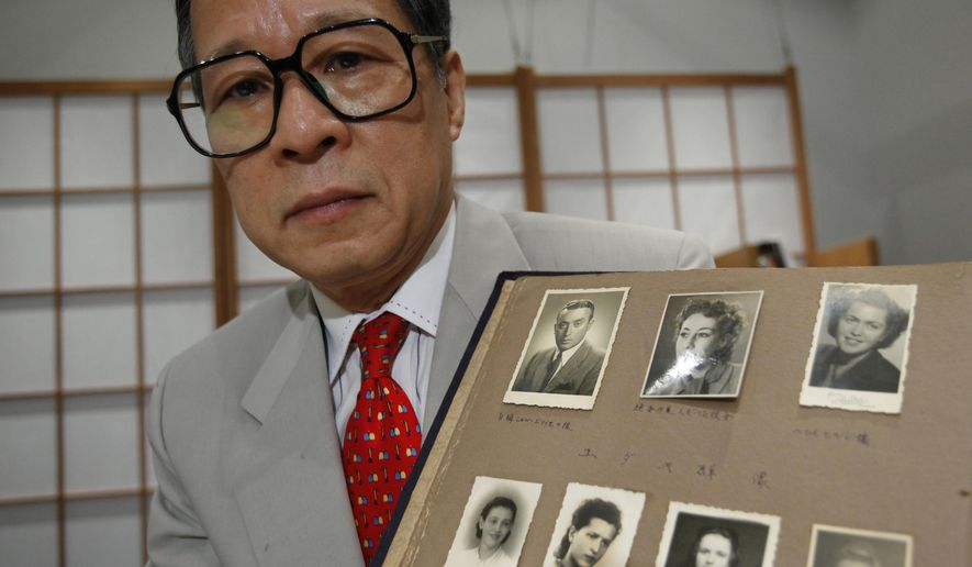 FILE - In this July 26, 2010 file photo, Akira Kitade holds a photo album that belonged to a former colleague of his at the  Japan Tourist Bureau, Tatsuo Osako, during an interview in Tokyo. The page displayed holds seven photos given to Osako by people whom Osako helped escape from Europe in the early days of World War II. Kitade, with the help of researchers in Japan and the U.S., has identified four of the seven people this year. A fifth was identified independently in 2014. Kitade met recently in the New York City area with descendants of three of the refugees who have been identified. (AP Photo/Shizuo Kambayashi, File)