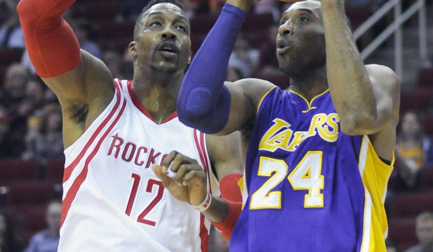 Kobe Bryant (24) looks to the basket guarded by Houston Rockets' Dwight Howard (12) in the first half of an NBA basketball game Saturday, Dec. 12, 2015, in Houston. (AP Photo/Pat Sullivan)