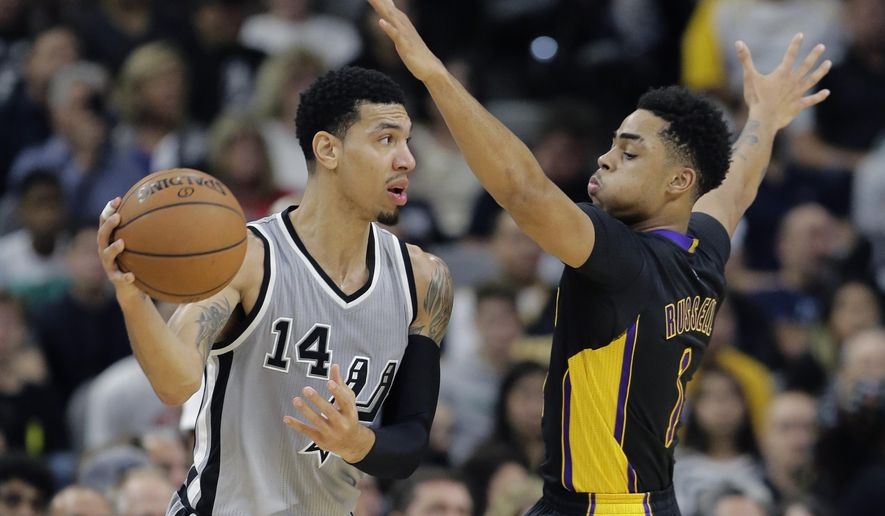 San Antonio Spurs guard Danny Green (14) is defended by Los Angeles Lakers guard D'Angelo Russell (1) during the first half of an NBA basketball game, Friday, Dec. 11, 2015, in San Antonio. (AP Photo/Eric Gay)
