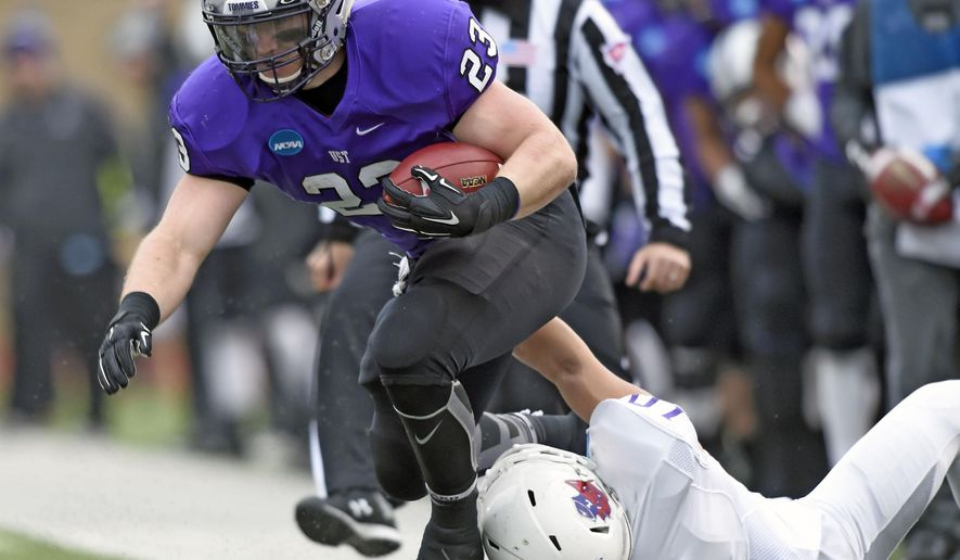 Linfield middle linebacker Skylor Elgarico (10) pulls St. Thomas running back Jordan Roberts (23) out of bounds during the first quarter during a Division III NCAA college football semifinal game on Saturday, Dec. 12, 2015, in St. Paul, Minn. (AP Photo/Hannah Foslien)