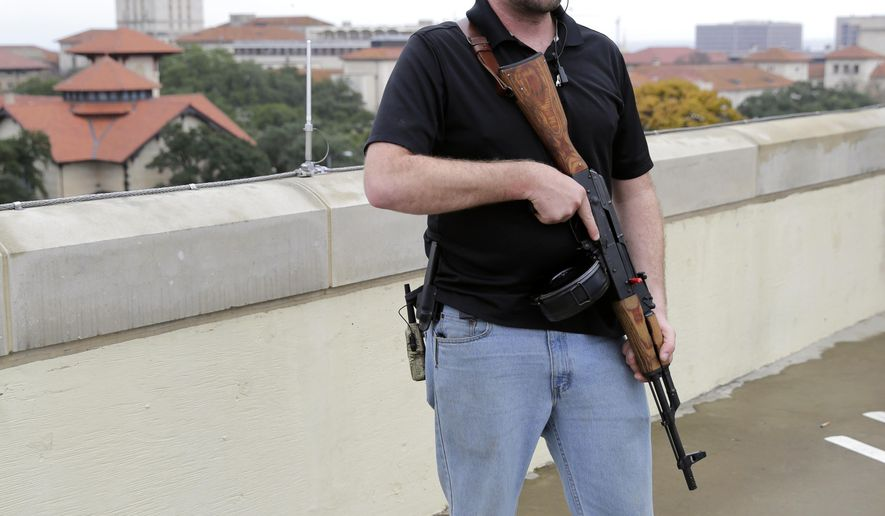 Gun rights activist Michael Short holds a gun as he prepares for a march near the University of Texas, Saturday, Dec. 12, 2015, in Austin, Texas. The group is planning a mock mass shooting near the campus. (AP Photo/Eric Gay)