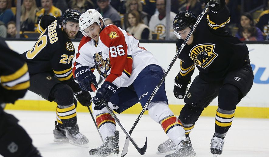 Florida Panthers' Connor Brickley (86) battles Boston Bruins' Landon Ferraro (29) and Kevan Miller, right, for the puck during the first period of an NHL hockey game in Boston, Saturday, Dec. 12, 2015. (AP Photo/Michael Dwyer)