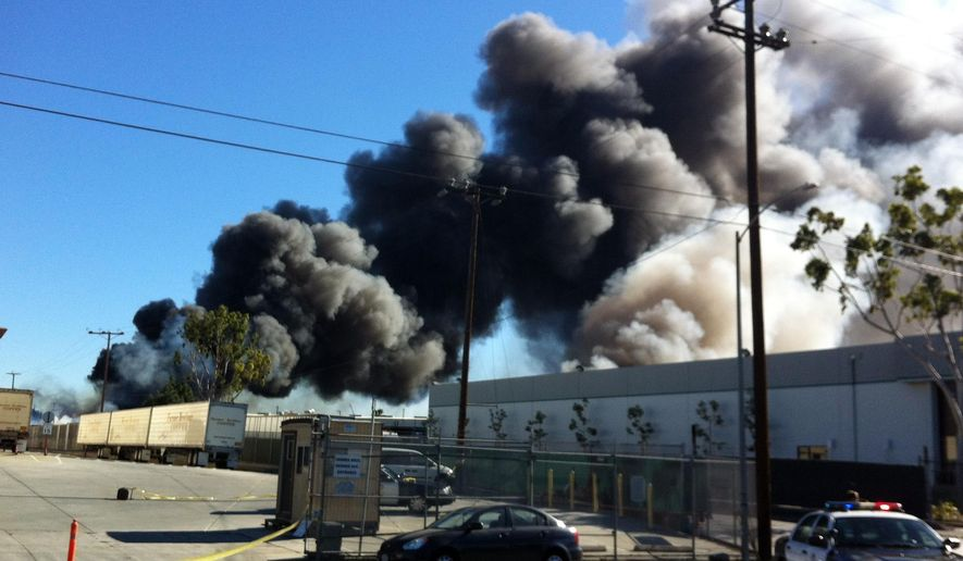 A huge plume of smoke, visible for miles across southern Los Angeles County, looms up over a burning recycling facility in an industrial area of Los Angeles adjacent to Torrance, Calif., Saturday, Dec. 12, 2015. Flames were reported around 10:15 a.m. Dozens of fire trucks responded and a tractor unit was requested to plow through debris at the site. No injuries were reported. (AP Photo/John Antczak)