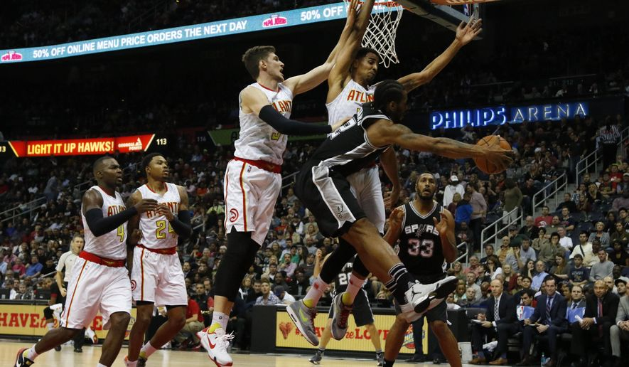 San Antonio Spurs forward Kawhi Leonard (2) passes to center Boris Diaw (33) while being defended by Atlanta Hawks forward Mike Muscala (31) and guard Thabo Sefolosha (25) as forward Paul Millsap (4) and forward Kent Bazemore (24) look on in the first half of an NBA basketball game Saturday, Dec. 12, 2015, in Atlanta. (AP Photo/Brett Davis)